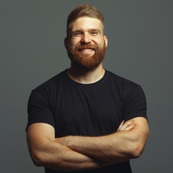 Fabulous at any age. Emotive portrait of laughing charismatic muscular 30-year-old man standing over light gray background. Perfect haircut. Rocker, biker, hipster style. Studio shot