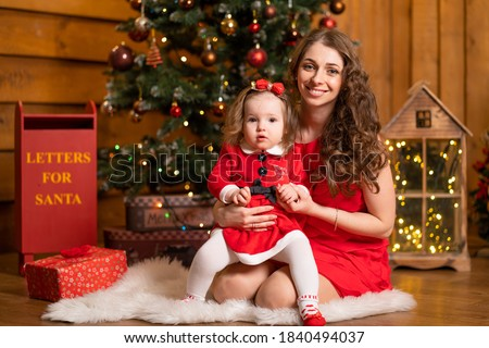 Fabulous Christmas holidays mom and daughter in red dresses decorate the Christmas tree. Cozy family holiday.