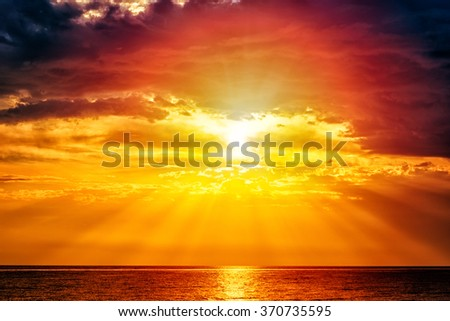 Fabulous landscape with sea and sky - yellow sun and deep red clouds above the water