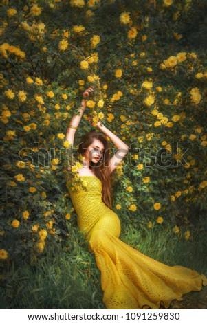 Fabulous sexy beauty in a long yellow dress, basking in a yellow rose Bush
