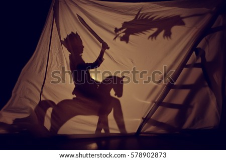 Fabulous the shadow of the little Prince on horse with sword and dragon. Theatre. Childhood. Tale.