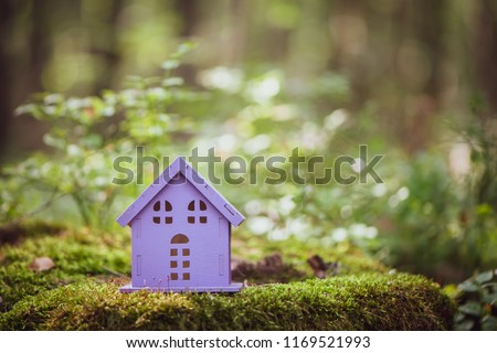 fabulous, toy house, the colors of lavender, against the backdrop of a fairy forest. Concept cozy home, cozy world. #1169521993