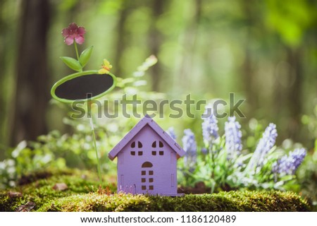 fabulous, toy house, the colors of lavender with a sign for inscription,  against the backdrop of a fairy forest. Concept cozy home, cozy world. #1186120489