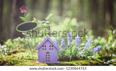 fabulous, toy house, the colors of lavender with a sign for inscription,  against the backdrop of a fairy forest. Concept cozy home, cozy world. #1230864763