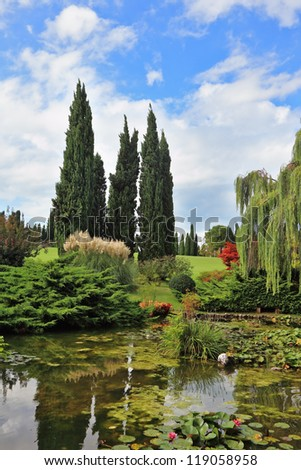 Fabulously beautiful Italian garden Sigurta. A pond with blossoming lilies. In the mirror of waters reflected cypress