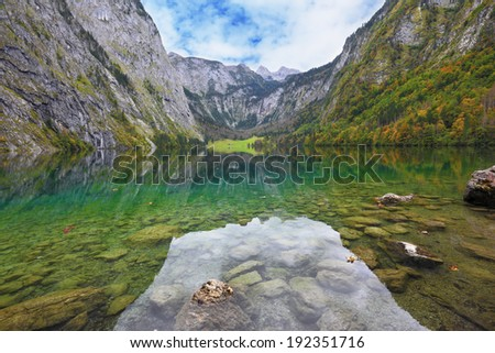 Fabulously beautiful lake Koenigssee. Mountainous lakeside reflected in the smooth water of the lake, like the wings of a butterfly