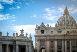 Facade and dome of The Papal Basilica of Saint Peter in the Vatican (Basilica di San Pietro), a Renaissance style church in Vatican City, within the city of Rome, Italy