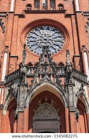 Facade fragment of zyrardow, żyrardów, church, rose window, rozeta, catholic, neo-gothic, red brick, towers, square, poland Zdjęcia stock ©