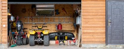Facade front view open door ATV quad bike motorcycle parking messy garage building with wooden siding at home driveway backyard and lawn path. House warehouse for tools and equipment . Wide panoramic