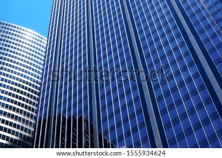 Facade of a blue modern office building close-up. Other skyscrapers are reflected in mirrored windows. Sun flare on the border of the roof and sky. Chicago, Illinois #1555934624