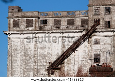 Facade of a derelict factory building with broken windows and crumbing concrete
