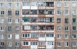 Facade of a grey multi-storey soviet panel building. Russian old urban residential houses with windows. Typical russian neighborhood.