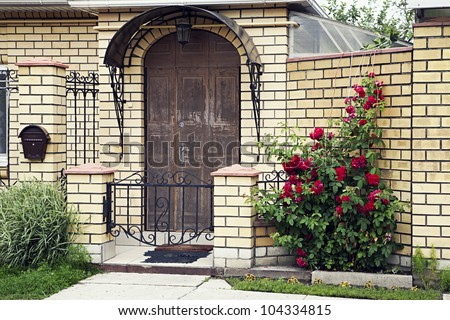 Facade of a little house with flowers in front of it