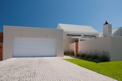 Facade of a modern house from the street with white walls, lavender plants, green lawn and garage driveway