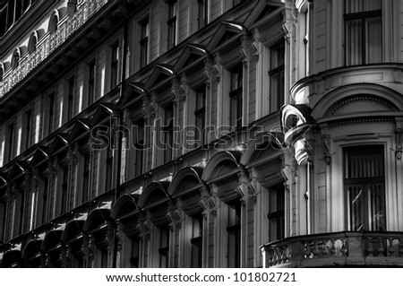 Facade of a old tradition building with many windows - black and white.