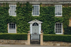 Facade of a traditional house in Broadway, Cotswolds, UK, covered with ivy.
