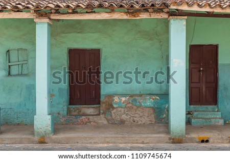 Facade of a turquoise and green vintage house in Santa Cruz de la Sierra, Bolivia, South America. A type of architecture style one can find throughout historic cities in Latin America.