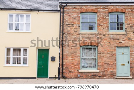 Facade of a Victorian house residential building in red bricks next to a modern build house