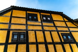 Facade of an old half timbered medieval house in northern Europe, with black wood window shutters and yellow chalk wall.
