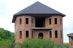 Facade of an unfinished two-story house with no red brick windows. Large house with rounded corners and a large terrace. The process of building a house on a large green plot near the forest.