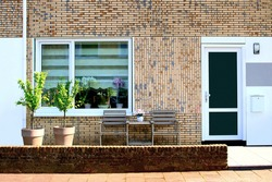 Facade of Dutch house, patio furniture in front yard garden and flower pots, neigborhood in the Netherands
