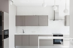 Facade of modern kitchen room at house with contemporary interior design, cabinet furniture, built in household appliance, sink, water tap, electric oven, stove and microwave near cooking hood