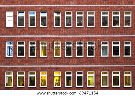 facade of office building in the evening with illuminated windows
