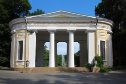 Facade of old building with columns, Flora Pavilion in the dendrological park Sofiyivka, Uman Ukraine. Fountain, trees and blue sky are the background.