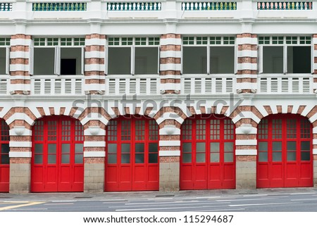 Facade of old fire station with red gates