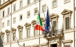 facade of Palazzo Chigi in Rome, seat of the Italian prime minister and government. The Italian and European flags on the balcony of the facade. Outdoors on a sunny day. Politics and democracy