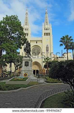 Facade of the Metropolitan Cathedral and statue of Simon Bolivar in the Parque Seminario (Iguana Park) near the center of downtown Guayaquil, Ecuador in early morning with a blue sky and white clouds