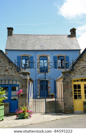 Facade of traditional breton houses with red and blue shutters, france