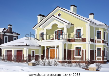 Facade of two-storey new cottage with garage at frosty and sunny winter day.