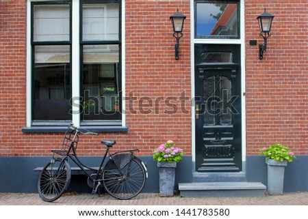 Facade of typical Dutch house with brick walls, steps, front door windows and black bike in popular neighborhood street, Netherlands Foto stock ©