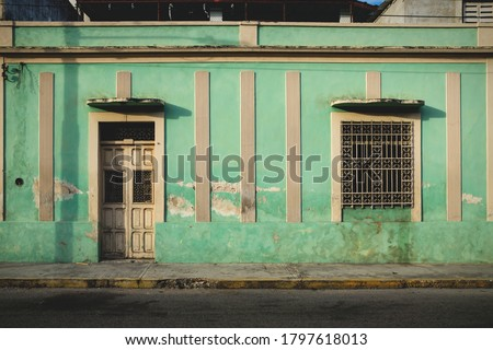 Facade of typical Mexican green abandoned colonial building in Merida, Yucatan, Mexico