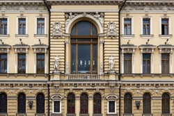 Facade palace building with sculptures, coats of arms and other architectural decorations front view