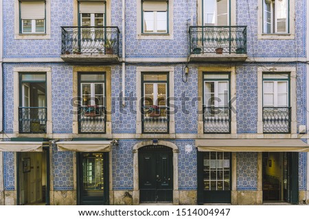 facade with typical portuguese tiles on the wall, picturesque lisbon architecture of tile facade with old windows and balcony at portugal