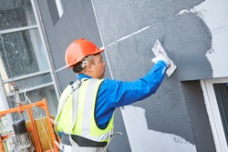 Facade worker plastering external wall of building
