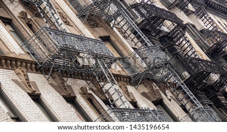 Facades of historic buildings in the Soho district of New York. The characteristic iron safety stairs on the facades #1435196654