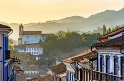 Facades of houses and church in colonial architecture in an old street in the city of Ouro Preto with the mountains in the background