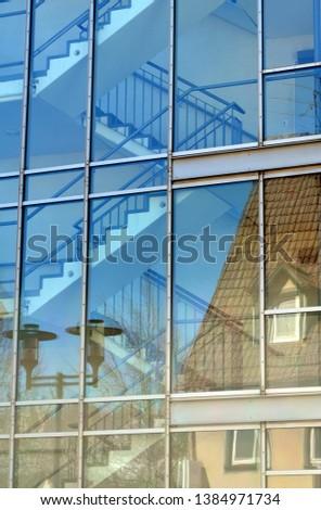 Facades of old houses reflect in a modern facade in Heidenheim #1384971734