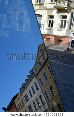 Facades of old houses reflect in modern glass facade in Freiburg #734209876