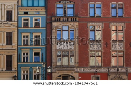 Facades of residential building in the center city Wroclaw. Old tenement house with windows, Row of historic tenement apartments.