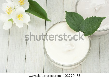 face and body cream moisturizers with jasmine flowers on white wooden, top view