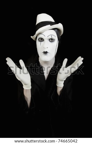 face and hands of mime with dark make-up on black background
