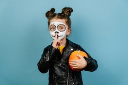 Face art and traditional Mexican holiday concept. Little girl child with orange pumpkin holding index finger at lips, asking to keep silence, dressed in Halloween costume, wears sugar skull makeup