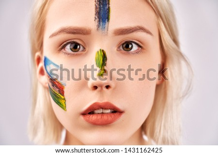Face art concept. Close up shot of beautiful female with attractive look, has artistic makeup in the form of paint strokes, looks thoughtfully directly at camera, isolated on background in studio.