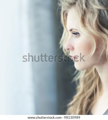 face beautiful blonde near a window