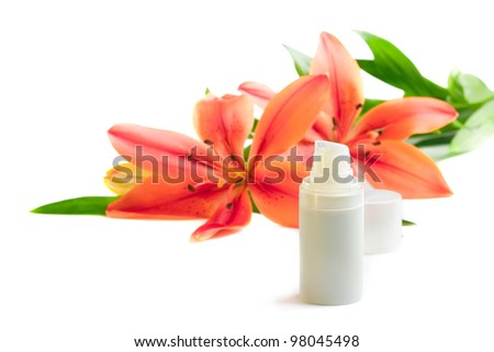 Face/body care concept: bottle of cream/lotion with lily flowers, closeup shot, on white