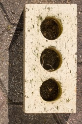Face brick used in construction of buildings. Note three holes which provide a